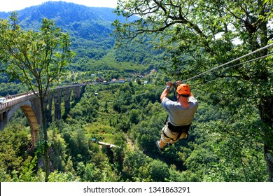 A man crosses over a long cable car over a mountain and forest across the Tiara River in Montenegro near the high stone bridge.