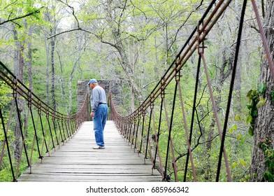 Man crossing aged Tishomingo stone and wood swinging bridge among greenery in dense forest.