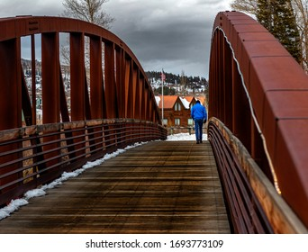 Man crossing the bridge on this cloudy morning