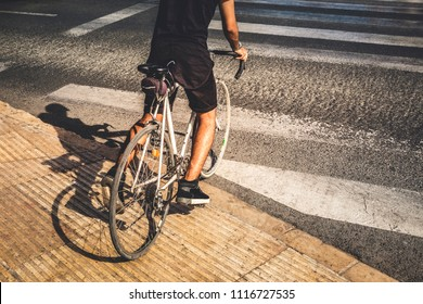 Man crossing a crosswalk with his old road bike, wearing casual clothes.