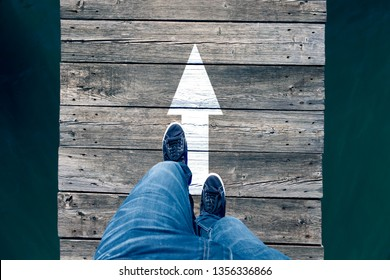Man crossing narrow wooden bridge with straight arrow sign. Personal perspective used.