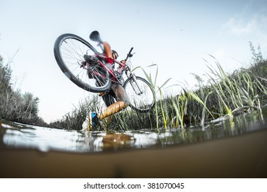 Man crossing the river with bicycle