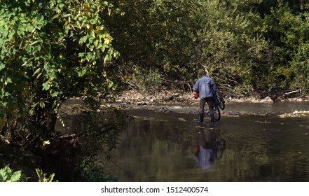 Man crossing river and holding his bicycle