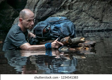 Man is crossing a river, pushing his backpack on hand-made raft. Concept of exploration and survival.