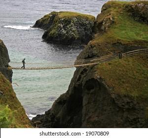 man crossing rope bridge in Ireland