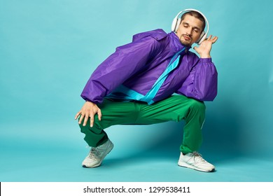 man crouches listening to music with headphones on a blue background
