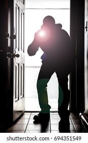 Man crouching at doorway threshold, in silhouette with flashlight crouching