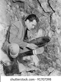 Man crouching and panning for gold