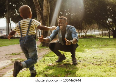 Man crouching at the park with his arms outstretched, with a boy running towards him. Son running into father's arms.