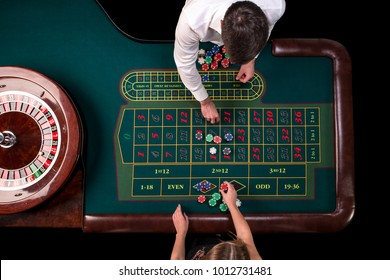 Man croupier and woman playing roulette at the table in the casino.