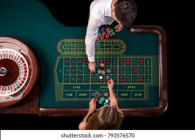 Man croupier and woman playing roulette at the table in the casino. Top view at a roulette green table with a tape measure.