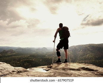 Man with a crutches in nature. Tourist with broken leg on crutches. Traveler with hurt leg in bandages stay on rocky  view point. Full length of man with broken leg.