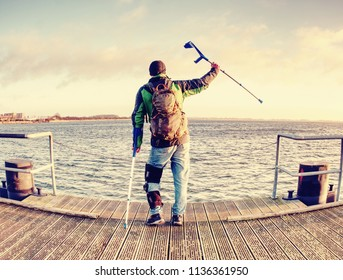 Man with a crutches on mole pier. Tourist with broken leg on crutches. Traveler with hurt leg in bandages. Full length of man with broken leg.
