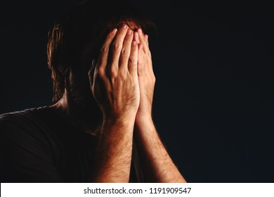 Man is crying in despair, hands covering face, low key portrait