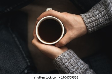 A man with a cup of coffee. A man drinks coffee sitting near the window