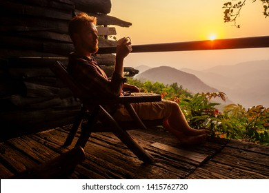man with cup of coffee tea enjoying the view from the balcony on tea plantation jungle at India Kerala Goa wildernest nature spa resort