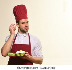 Man with curious face holds egg near ear. Cook in burgundy uniform with uncooked eggs. Baking and cooking concept. Chef with beard prepares to cook food on white background, copy space.