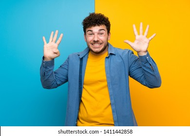 Man with curly hair over colorful wall counting nine with fingers