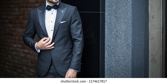 Man in custom expensive tailored tuxedo,suit posing outdoors