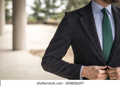 Man in custom tailored suit posing outdoors and buttoning his jacket