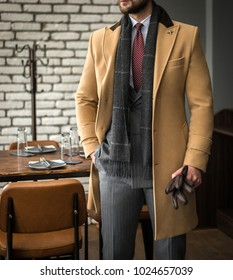 Man in custom tailored suit and trench coat posing indoors