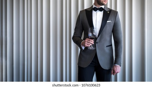 Man in custom tailored tuxedo, suit holding glass with wine and posing indoors in front of background