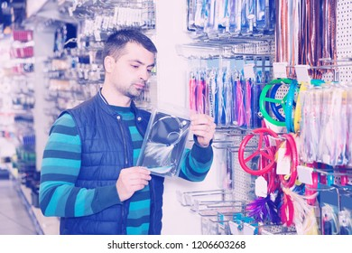 Man customer choosing fishing lures near stand in the sports shop
