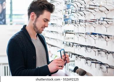 Man as customer choosing glasses from shelf in optician shop