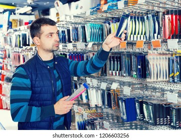 Man customer looking fishing lures near stand in the sports shop