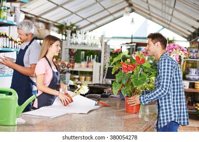Man as customer in nursery shop talking to woman at checkout