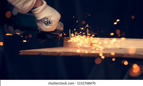 Man cut down the pin in wooden plank with lighting and cords using circular saw. Sparkles all over the place. Man at handmade diy work