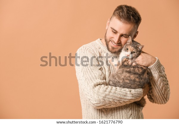 Man with cute cat on color background