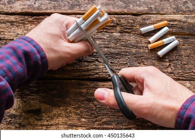 man cuts a cigarette with scissors