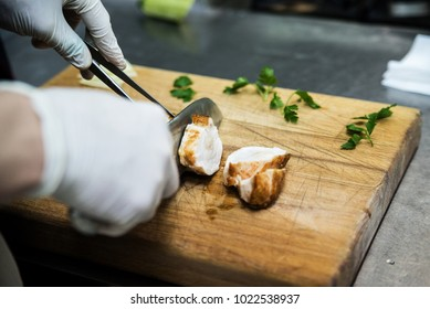 The man cuts meat on cutting board using his knife