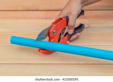 Man cuts off a piece of polypropylene pipes. On a wood background.