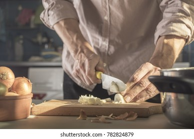 Man cuts onions in the kitchen