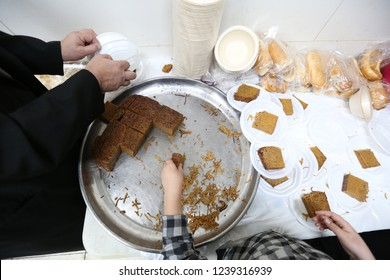 """Man cuts and serves traditional Jewish food called """"Yerushalmi kugel"""" which is a noodle souffle cooked with burnt sugar"""