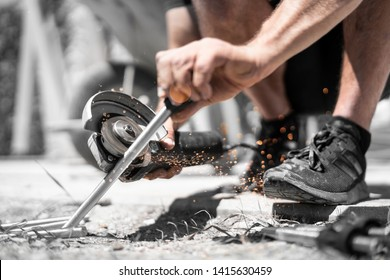 Man cuts threaded rod with electric one-hand grinder and flex on the construction site  and the sparks fly