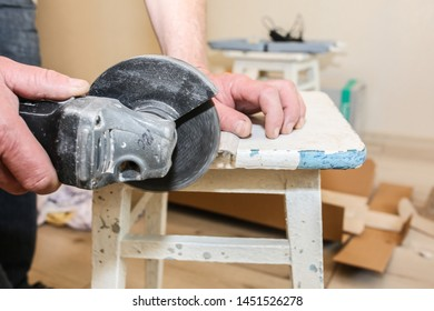 Man is cutting baseboard. Repair works indoors. Renovation in the flat.  Angle grinder in hands.