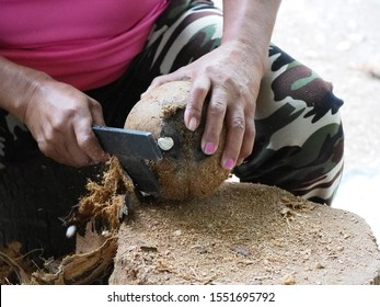 The man is cutting the coconut peel by using axe