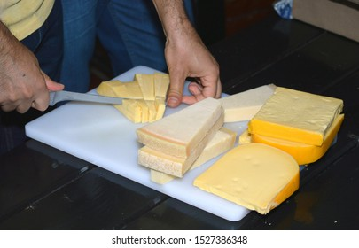 Man cutting different cheese types with knife on white cuttingboard.