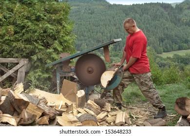 man cutting firewood, preparing for winter