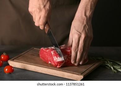 Man cutting fresh raw meat on wooden board