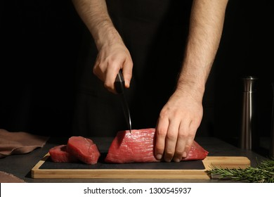 Man cutting fresh raw meat on table against dark background, closeup