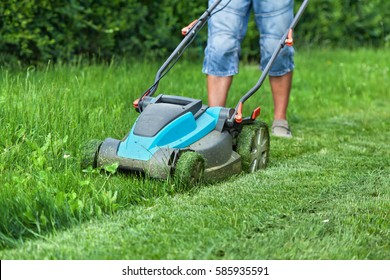 Man cutting the grass with a lawn mower - detail