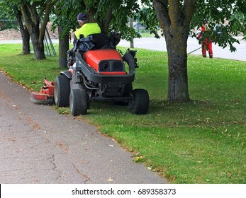 Man cutting the grass of  on a tractor lawn mower
