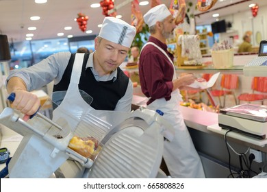Man cutting meat with industrial machine