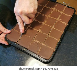 A man cutting the Millionaire's shortbread in the oven tray.