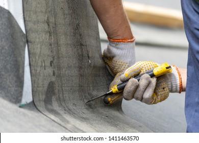 Man schneidet einen Teil der wasserdichten Bitumenmembran mit Messer. Nahaufnahme, Schnittbild des Dachdeckers, der auf dem Dach des neuen modernen Hauses arbeitet. Konzept des Wohngebäudes im Bau