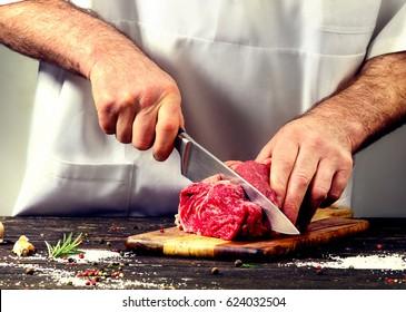 Man cutting raw beef meat.